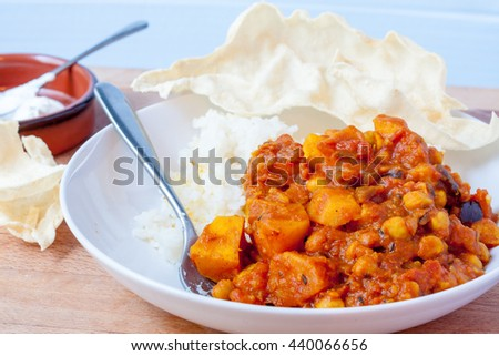 A bowl of potato and chickpea curry with white rice with poppadums and yogurt
