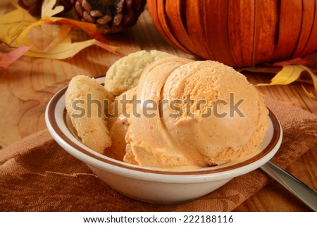 A bowl of pumpkin ice cream and sugar cookies on a holiday table - stock photo
