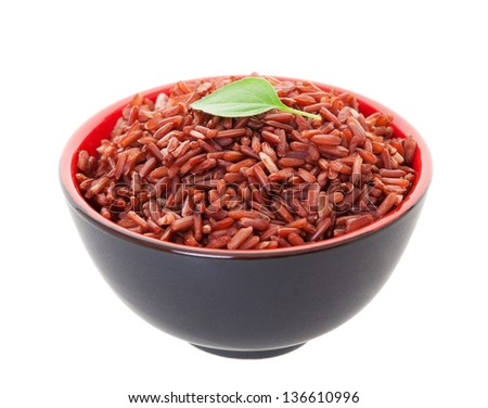 A bowl of Red Cargo Rice garnished with a single leaf of lemon basil.  Shot on white background. - stock photo