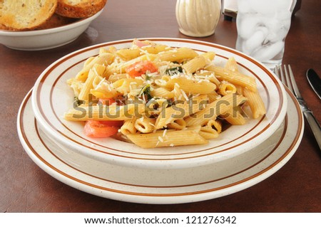 A bowl of rigatoni with parmesan and romano cheese, spinach and tomatoes
