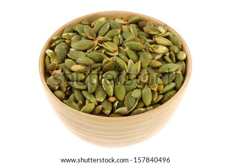 A bowl of Roasted and Salted Pumpkin seeds, isolated on white background - stock photo