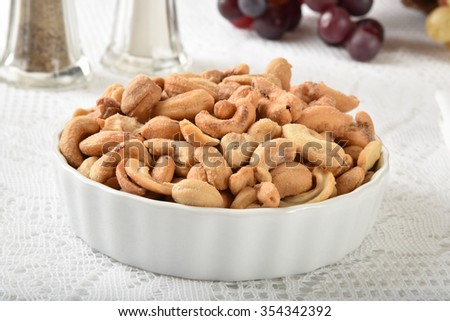 A bowl of roasted salted cashews on a white lace tablecloth - stock photo