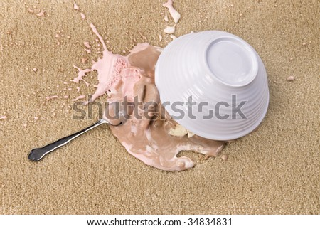 A bowl of spilled Neapolitan ice cream on white carpet that is melting. - stock photo