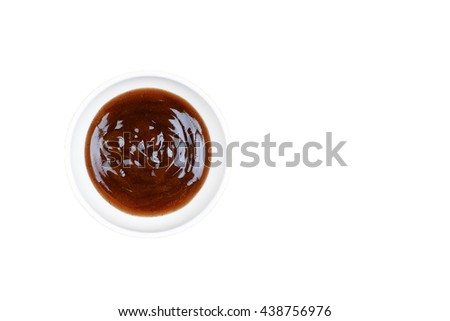 A bowl of thick black pepper sauce in white bowl over white background. - stock photo