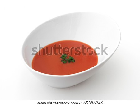 A bowl of tomato soup on a white background. - stock photo