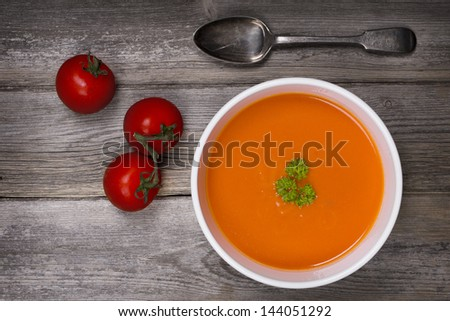 A bowl of tomato soup with a tarnished silver spoon and fresh vine tomatoes, against a rustic wood tabletop. Vintage style with intentional vignette and selective desaturation - stock photo