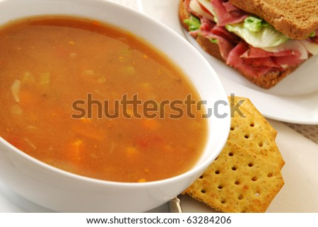 A bowl of vegetable soup and a roast beef sandwich - stock photo