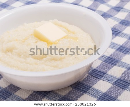 A bowl of white corn grits on a blue plaid placemat - stock photo