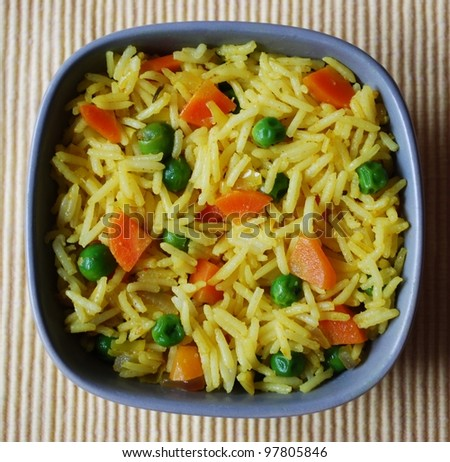 A bowl of yellow basmati rice with carrots, peas, onion and curry - stock photo