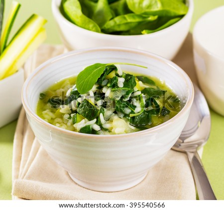 A bowl with rice, spinach and zucchini, served like a soup. - stock photo