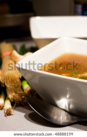 A bowlful of chicken broth soup with ingredients - stock photo