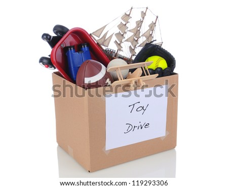 A box full of toys and sports equipment for a holiday charity drive. Isolated on white with reflection. - stock photo