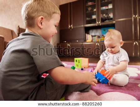 A boy aged 3 and a girl aged 1 are playing on the floor - stock photo