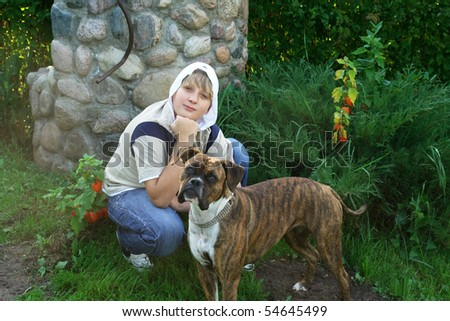 A boy and a dog near a well in the garden - stock photo