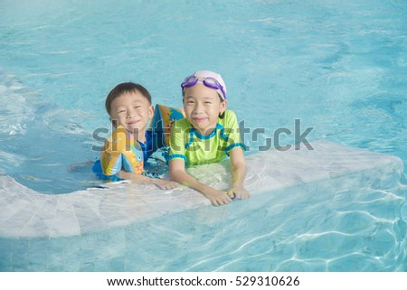 A boy and a girl are playing at the swimming pool