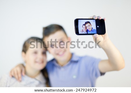 A boy and a girl taking a self portrait with smart phone against gray background - stock photo
