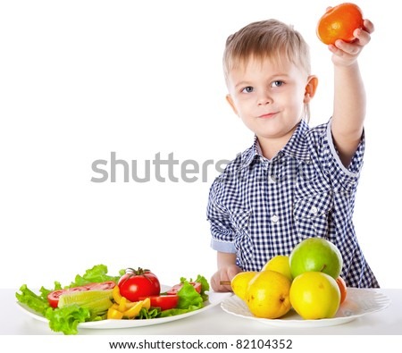 A boy and the plate of vegetables and fruits. Isolated on a white background - stock photo