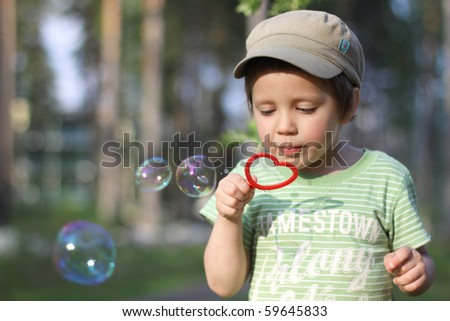 A boy blowing bubbles - stock photo