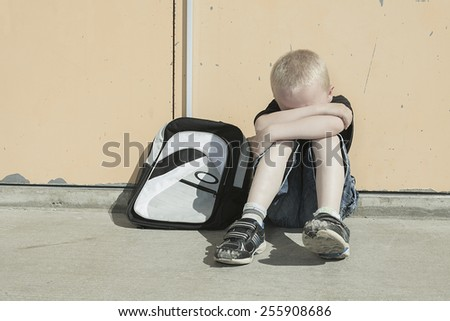 A boy bullying in school playground. very sad! - stock photo