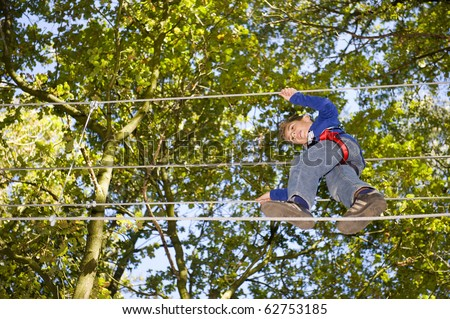 a boy climbing in adventure park