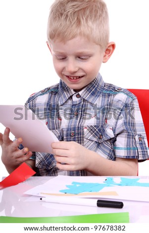 A boy cutting paper with scissors, isolated on white