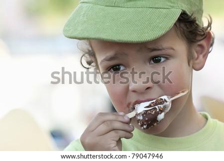 A boy eating an ice cream outdoor - stock photo