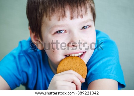 A boy eats a ginger biscuit
