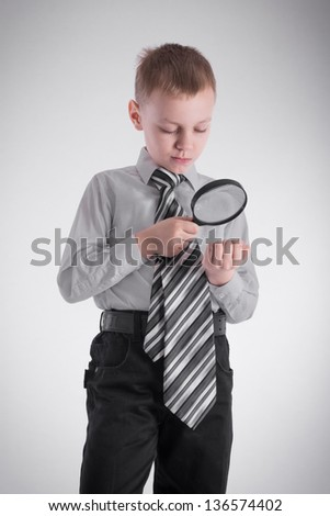 A boy examines his hand with a magnifying glass - stock photo