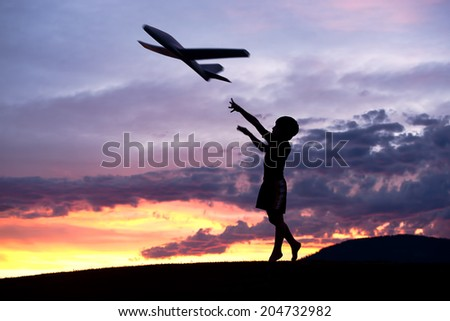 A boy flies a toy plane at sunset on the Rathdrum Prairie in north Idaho. - stock photo