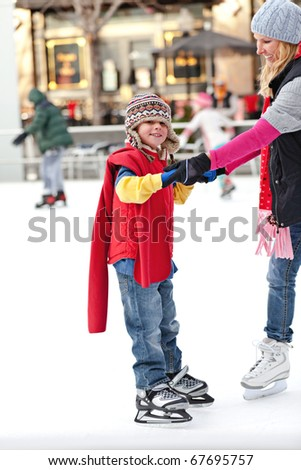 A boy hangs on to his mother while learning to ice skate. - stock photo