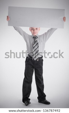 A boy holding nameplate over his head