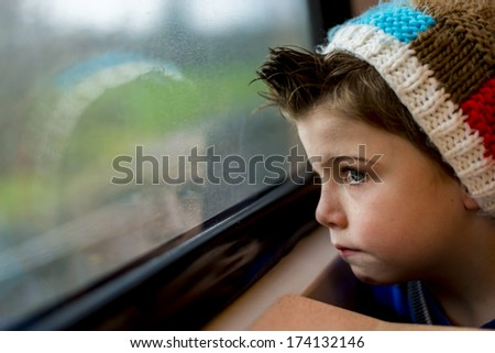 a boy in a train staring through a window - stock photo