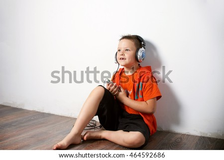 a boy in an orange shirt and black shorts sitting on the floor near white wall background and listening to music on headphones