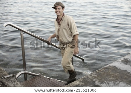 a boy in old retro clothes and cap standing by the water looking poor and dirty, an apprentice - stock photo