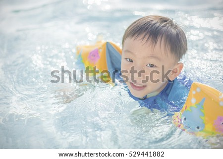A boy in swimming suit at the swimming pool