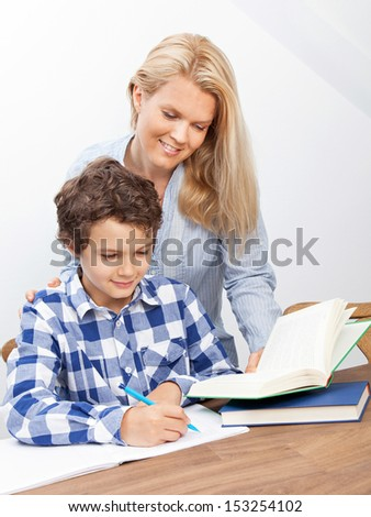 A boy is doing his homework and his mother is helping him with it. They look very happy. - stock photo