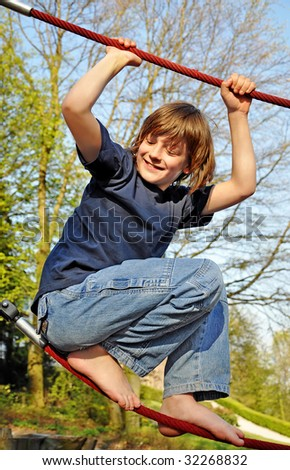 a boy is having fun with holding himselve on a red rope, standing on another red rope