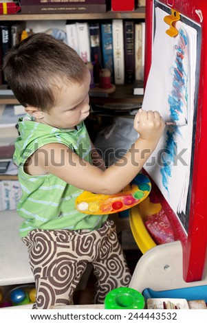 A boy is painting by brush on the easel