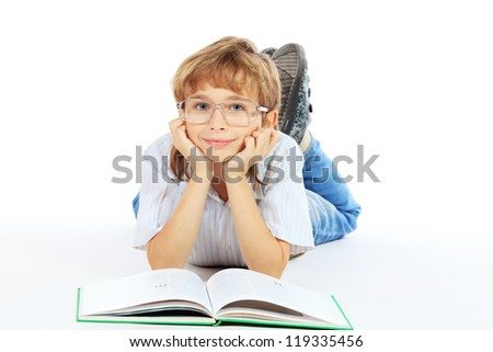 A boy is reading his book lying on a floor. Isolated over white background.