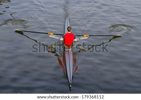 A boy is rowing with a red jacket in manzanares river, Madrid, Spain - stock photo