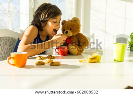 A boy is sitting and eating with Teddy bear