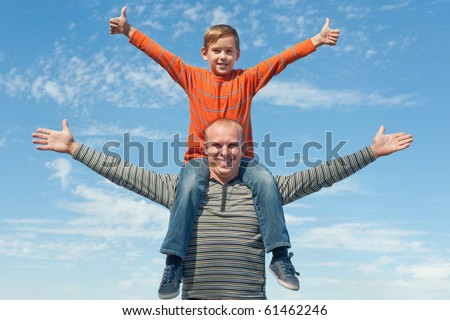 A boy is sitting on his father's neck holding his thumbs up - stock photo