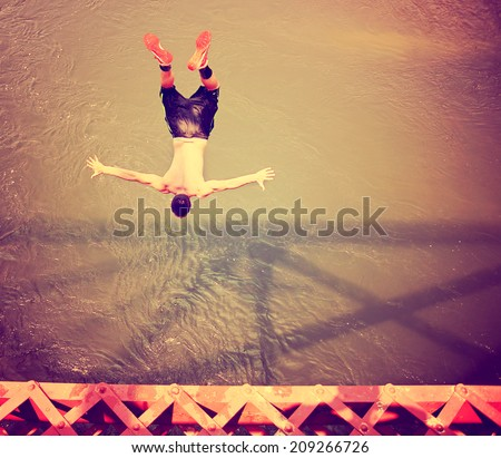 a boy jumping of an old train trestle bridge into a river toned with a retro vintage instagram filter  - stock photo