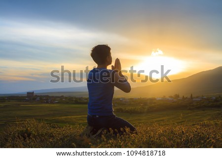 A boy kneeling and praying