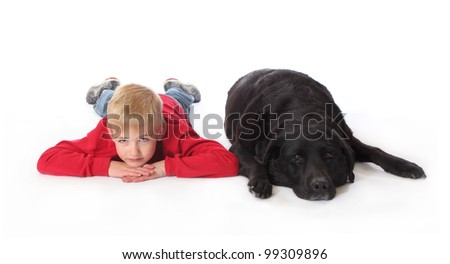 A boy lays on the floor next to a black lab.
