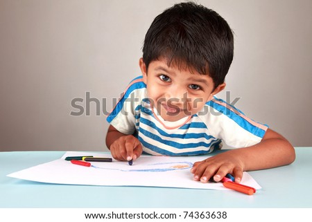 A boy looking while painting on a white paper - stock photo
