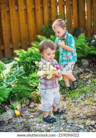 A boy looks for Easter eggs during an egg hunt while his little brother plays with a plush toy bunny rabbit outdoors in a garden.  Part of a series. - stock photo