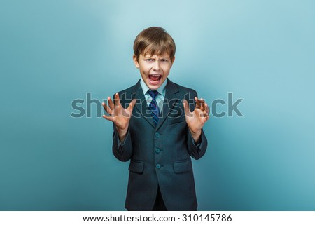 a boy of twelve European appearance in a suit shouting angry on a gray background - stock photo