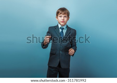 a boy of twelve European appearance in a suit shows his fists on a gray background - stock photo