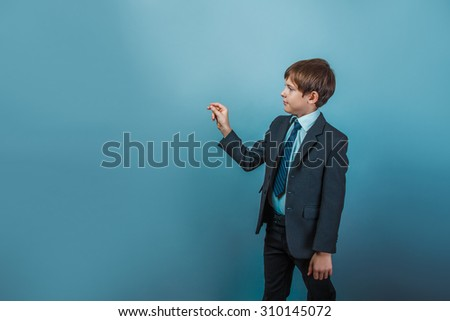 a boy of twelve European appearance in a suit writing in the air invisible pen on a gray background - stock photo